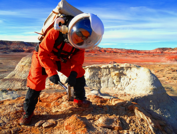 Female geologist wearing gear and holding a chisel