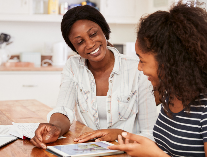 Mother and young daughter sat at kitchen table looking at tablet and smiling