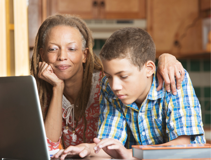 Mother with arm around her son's shoulders as he uses a laptop