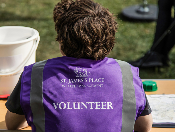 Person with short hair wearing St James' Place volunteer top, supporting DofE