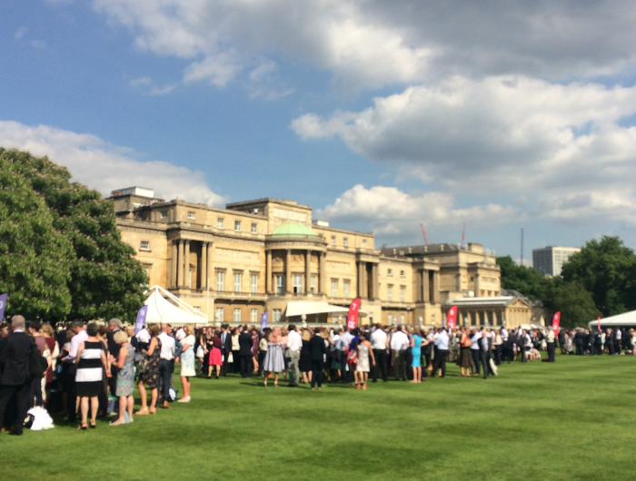 Large crowd of people stood on lawn in front of Buckingham Palace at DofE Gold Awards Presentation