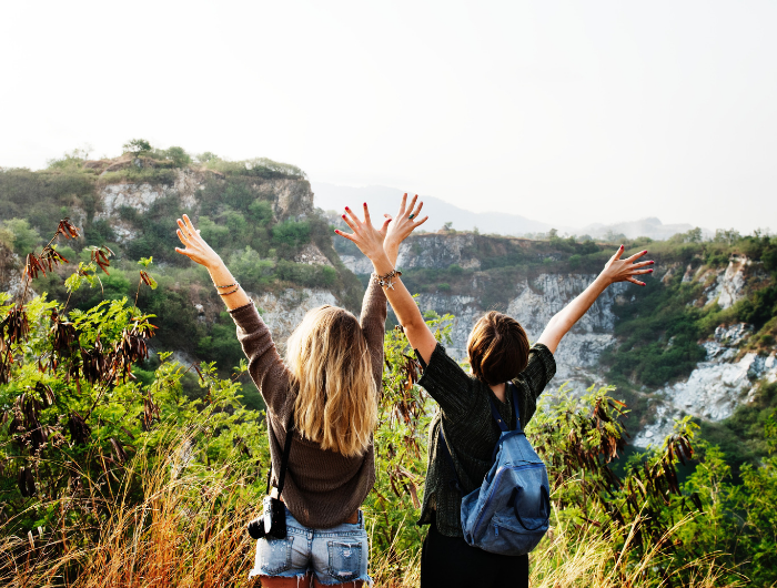 Two young women facing away with hands in the air stood at the top of a hill