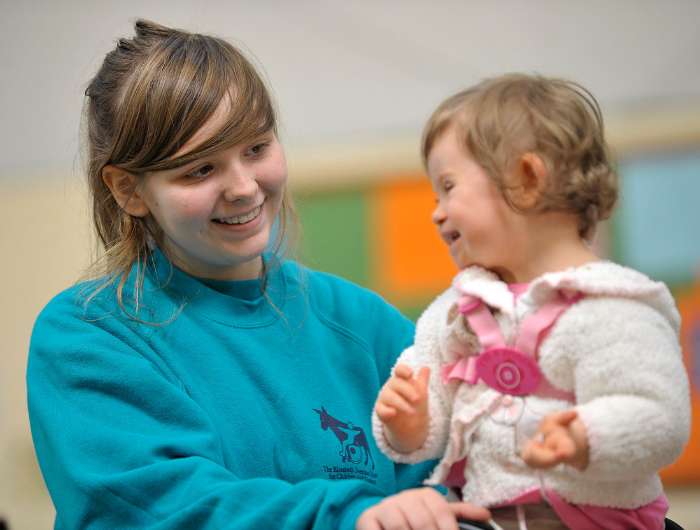 Teenage girl doing her DofE volunteering smiling and playing with a young child