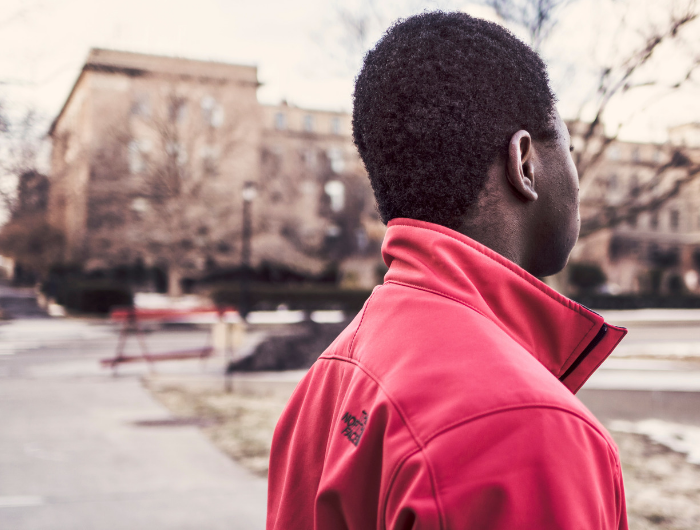 Young man in red jacket stood on street facing away