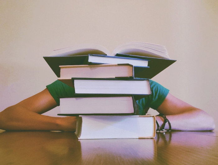 Pile of books on table with person slumped behind so you can only see their arms