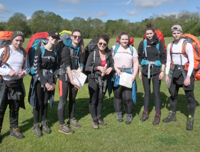 Group of young people stood in a field wearing backpacks ready for their DofE expedition