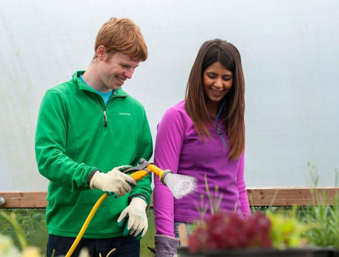 Young man watering plants while young woman watches and smiles