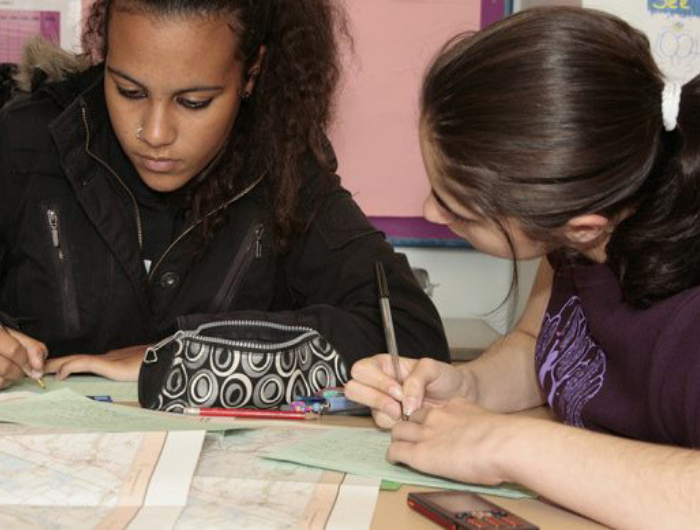 Two young girls studying maps together