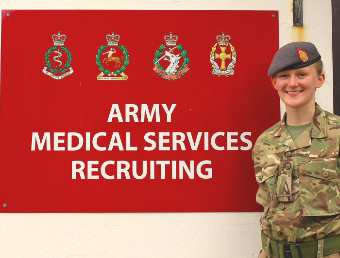 Young woman Caroline wearing army uniform stood in front of Army Medican Services Recruiting sign