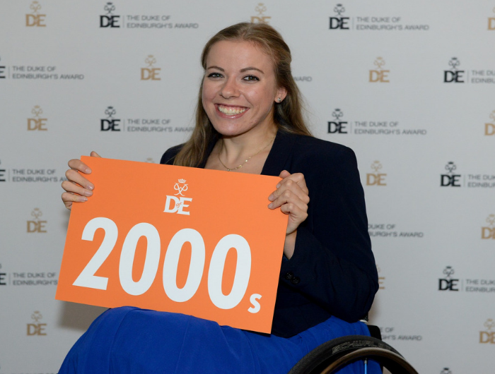Young woman Hannah in wheelchair holding orange DofE 2000s sign