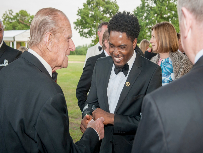 Young man Raphael shaking hands with the Duke of Edinburgh and smiling