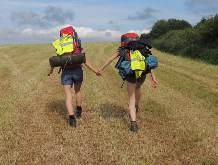 Two girls holding hands climbing a hill wearing backpacks