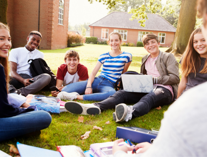 Group of young people sat in a circle on grass smiling and chatting