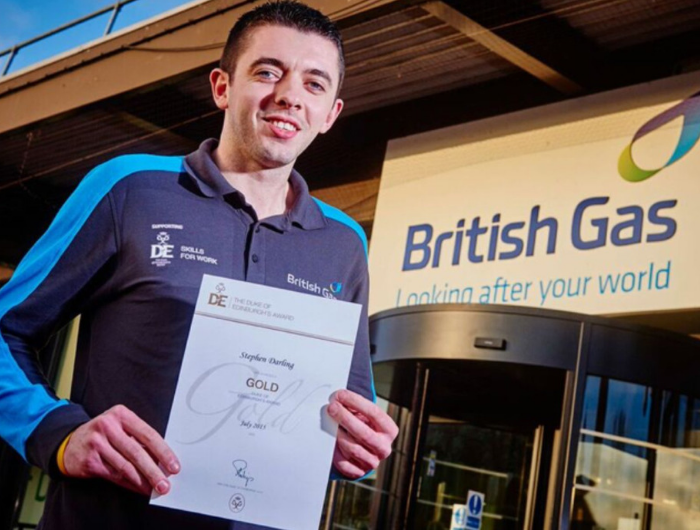 Young man Stephen holding certificate in British Gas uniform and in front of sign
