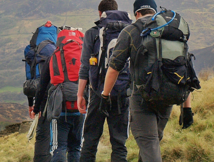 Group of young people walking on a hill in backpacks on a DofE expedition