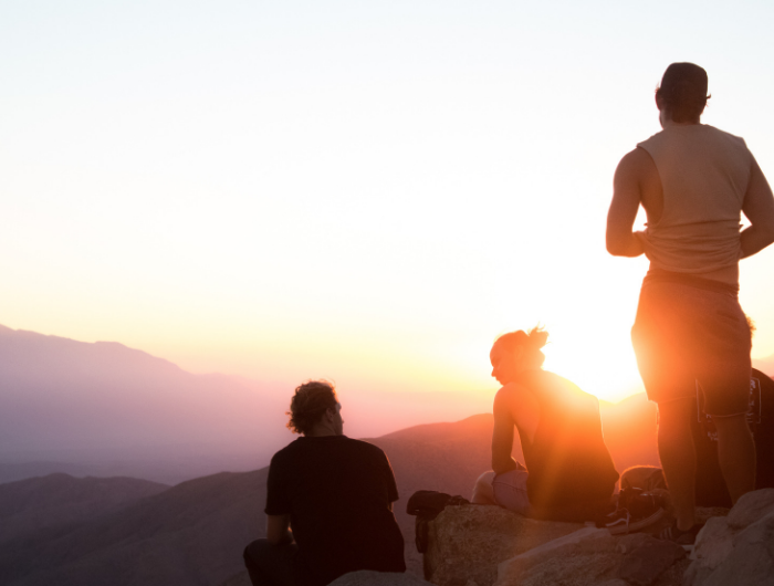 Three young people looking at a sunset on a mountain