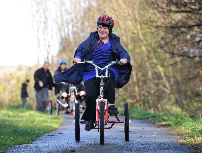 Young girl Kirsty on an electric trike cycling along a path
