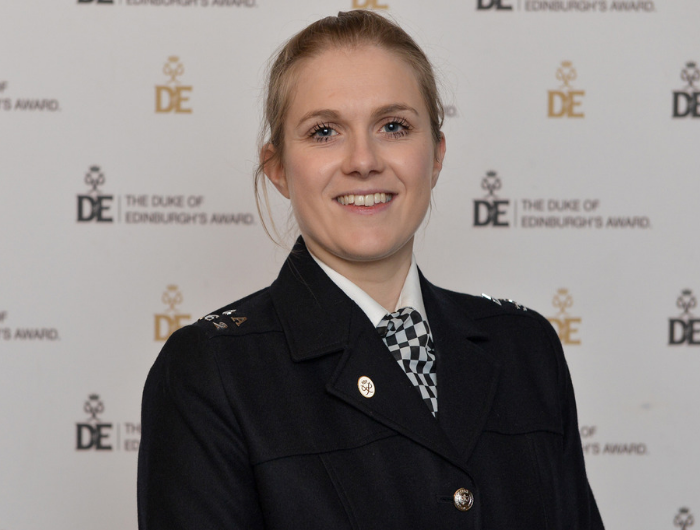 Young woman Sophie in police uniform stood in front of DofE logo wall