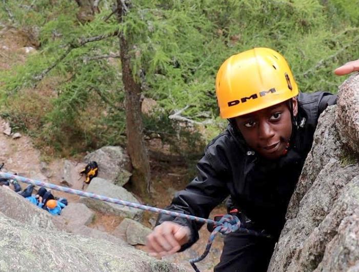 Young boy mountain climbing wearing helmet
