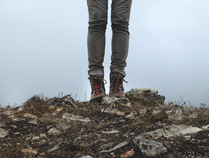 Woman in hiking boots stood on top of a hill