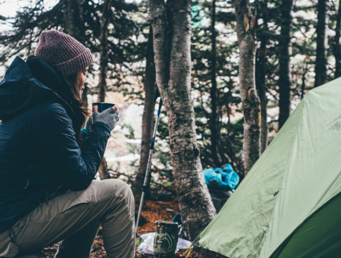 Woman in winter gear drinking a hot drink sat next to tent