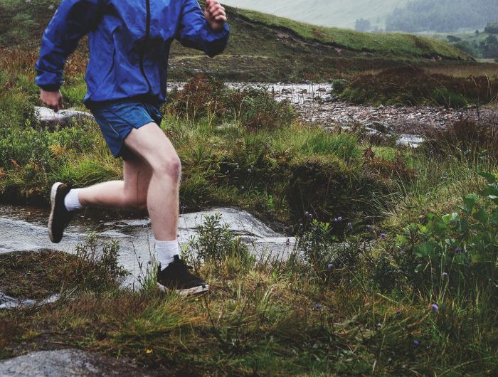 Young man running along uneven ground in trainers