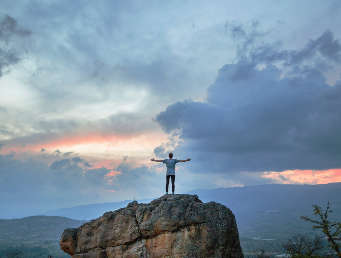 Young man stood on top of rock with arms stretched in the air