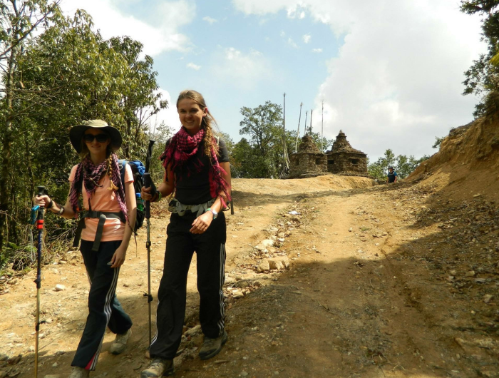 Young girl Sophie and friend walking along with hiking sticks on DofE expedition