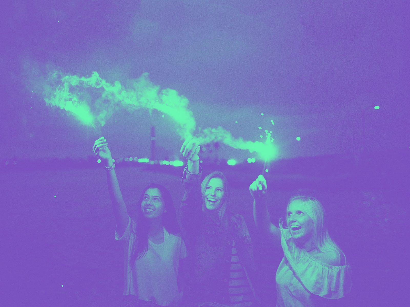 Three women smiling holding sparklers