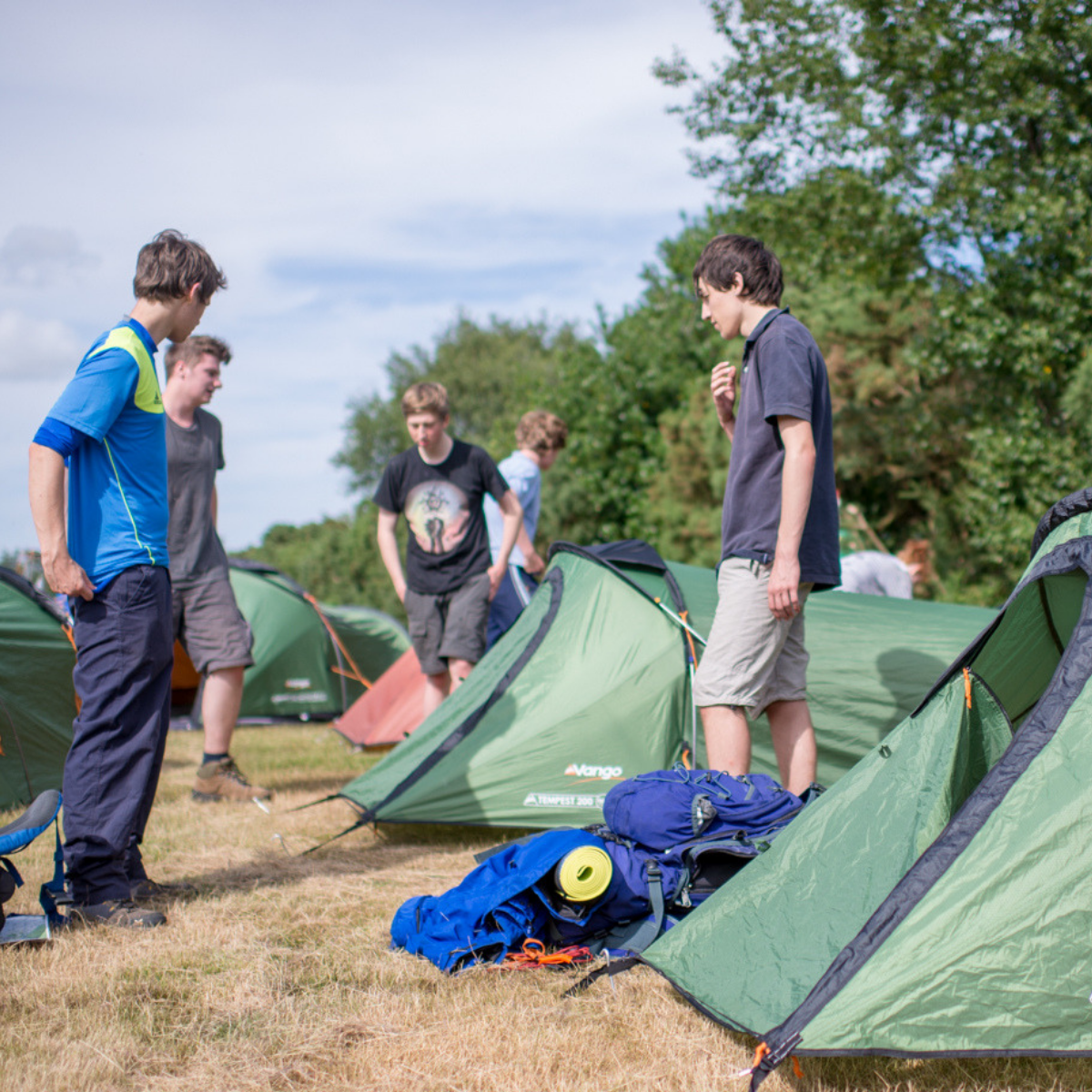 Group of boys stood around tents
