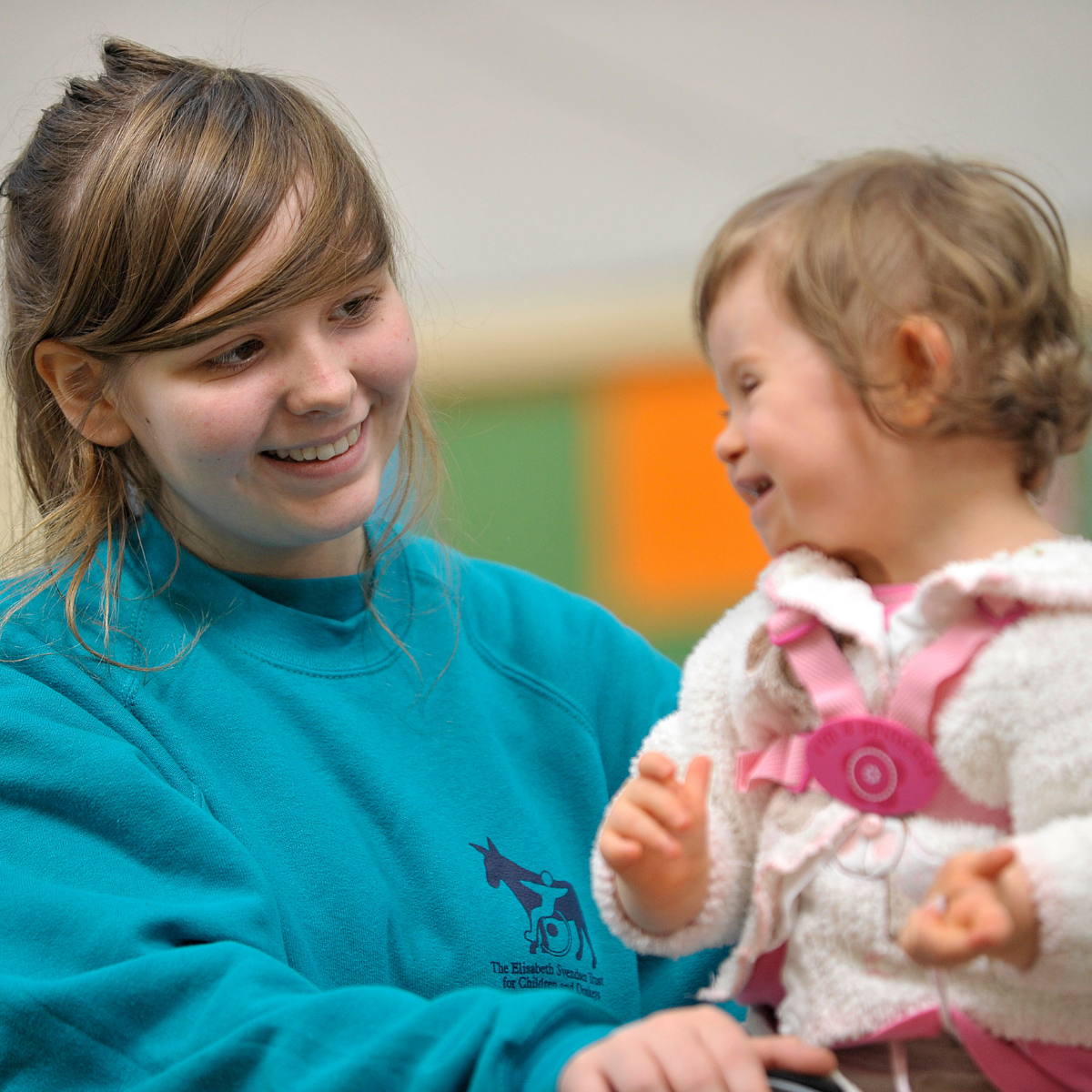 Young girl playing with a child as a volunteer