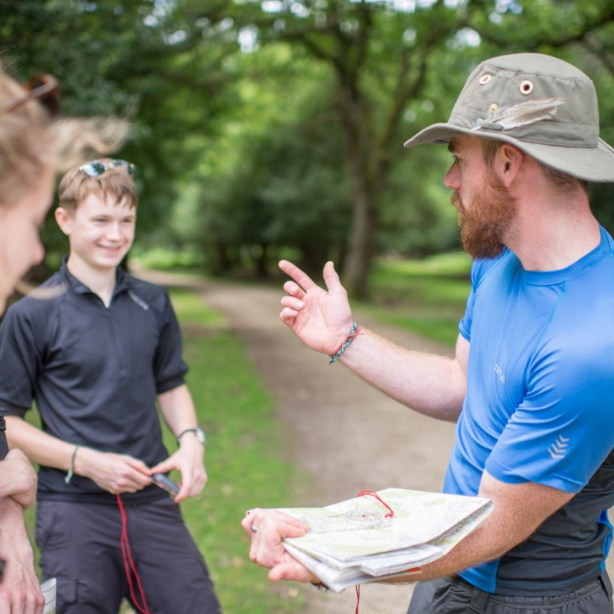 Man teaching two young people to read maps