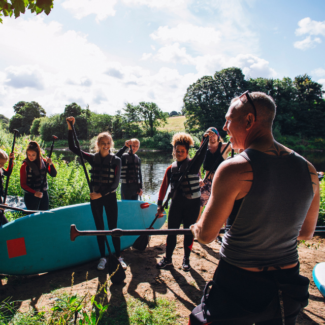 Leader with group of young people ready to paddleboard