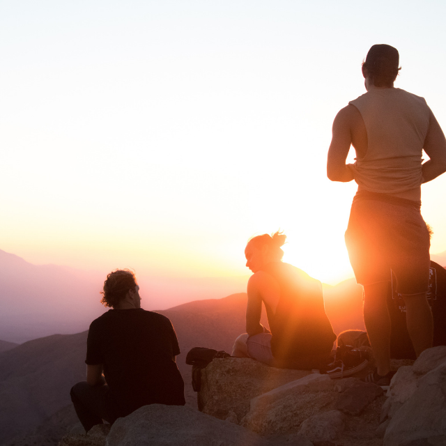 Group of people on a hill watching sunset