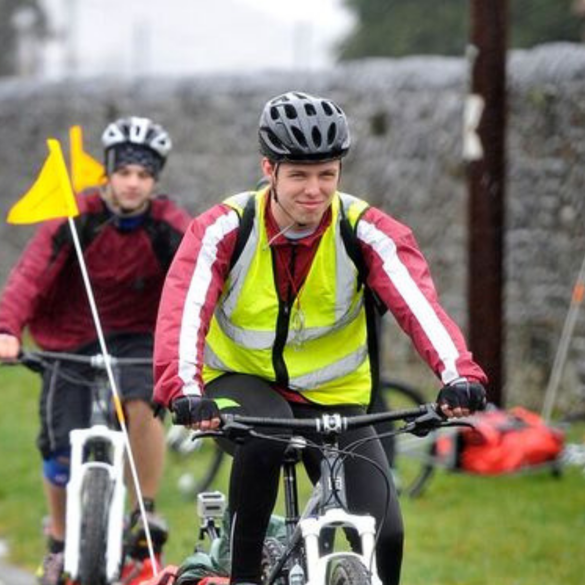 Two young people riding bikes with yellow flags wearing helmets