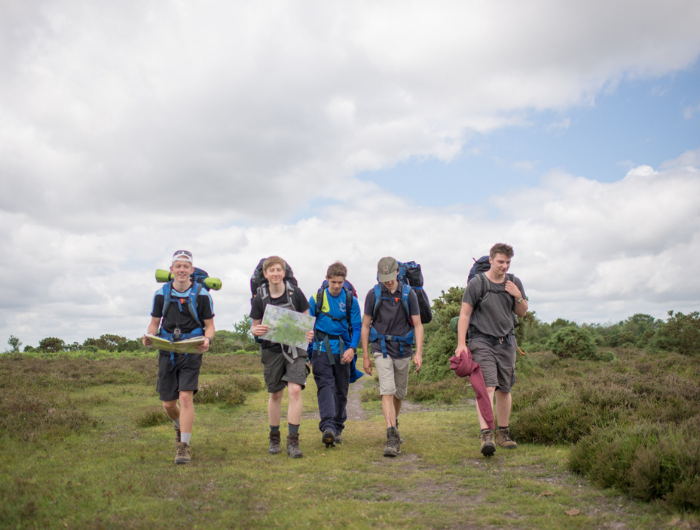 Group of young people on expedition walking up a hill with backpacks on