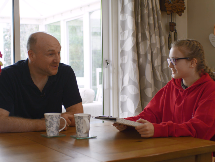Young girl Carys sat at dining table talking to her Dad about her DofE Award