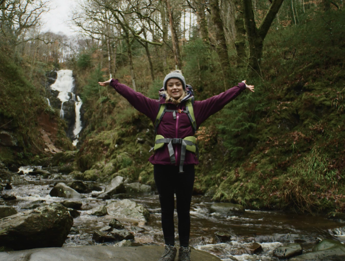 Young girl Elle stood in woodlands wearing DofE expedition gear with her hands in the air smiling