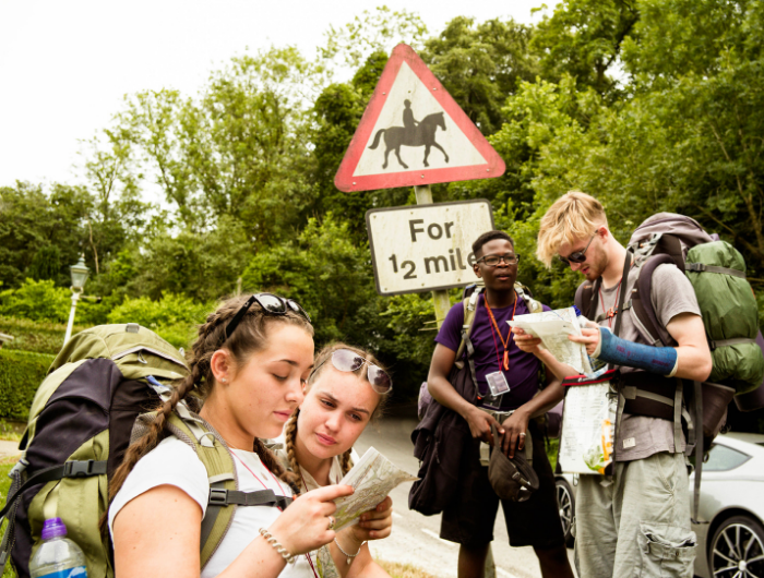 Group of young people on DofE residential expedition stood reading maps at the side of a road