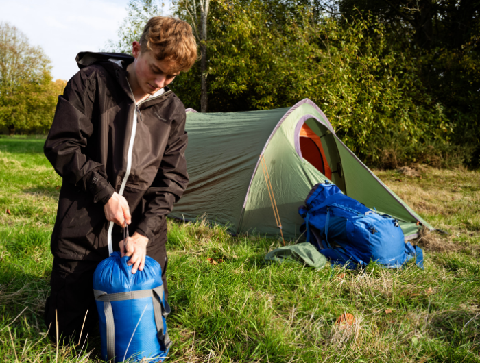 Young male on expedition packing up tent