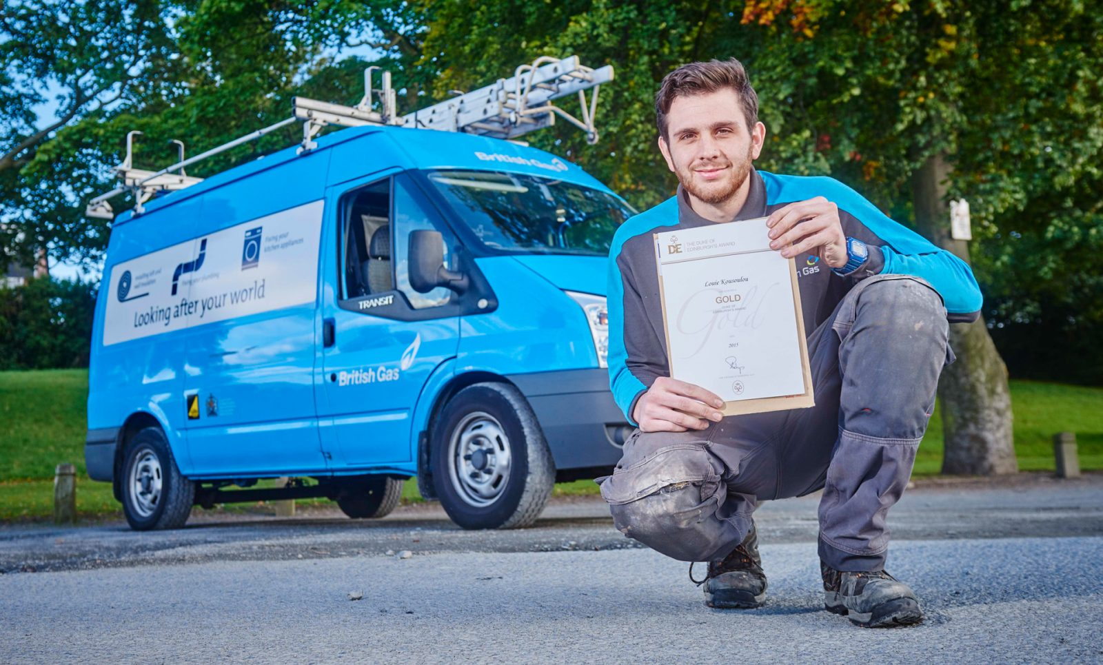 British Gas male apprentice kneeling with Gold DofE certificate
