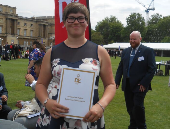 Award holder Kira Jarvis holding Gold certificate in Buckingham Palace Gardens