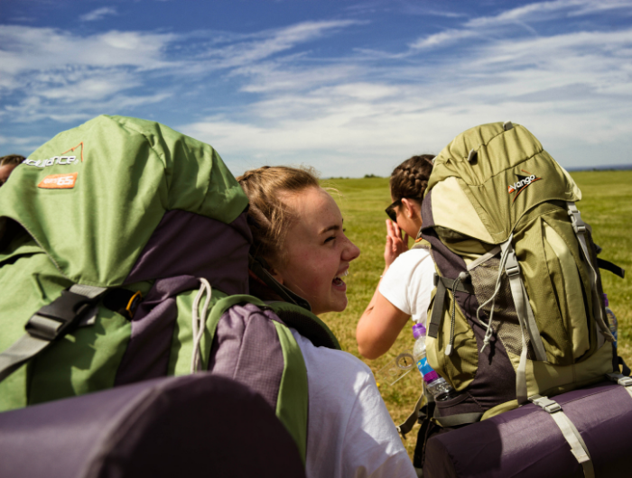 Two girls laughing on expedition wearing rucksacks