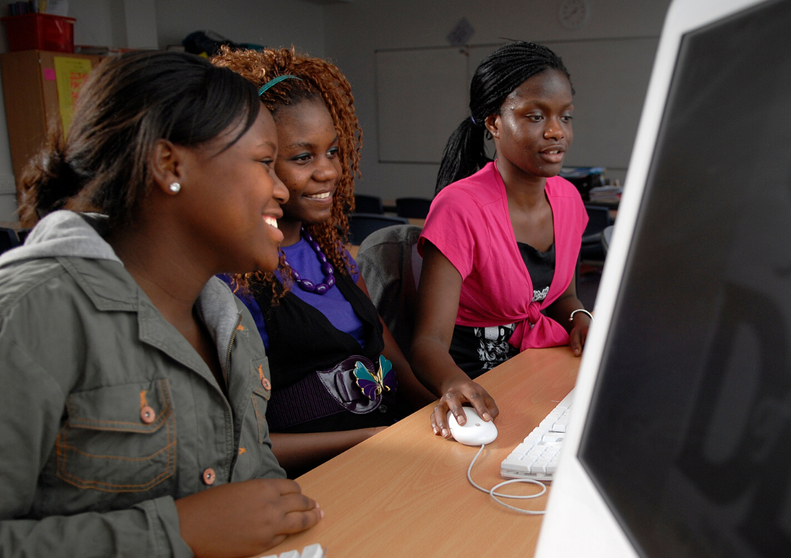Three black young women working at a computer