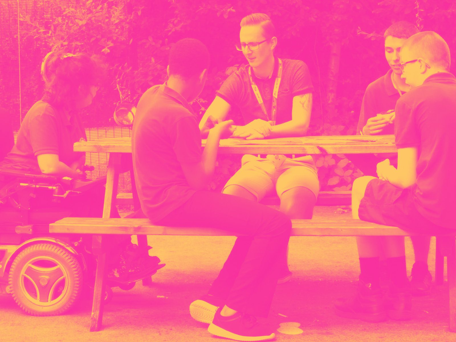 Group of participants and a Leader talking sitting on picnic bench