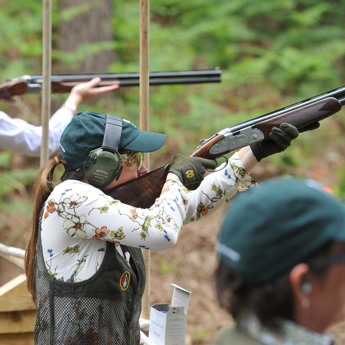Three people holding shotguns at clay pigeon shooting event