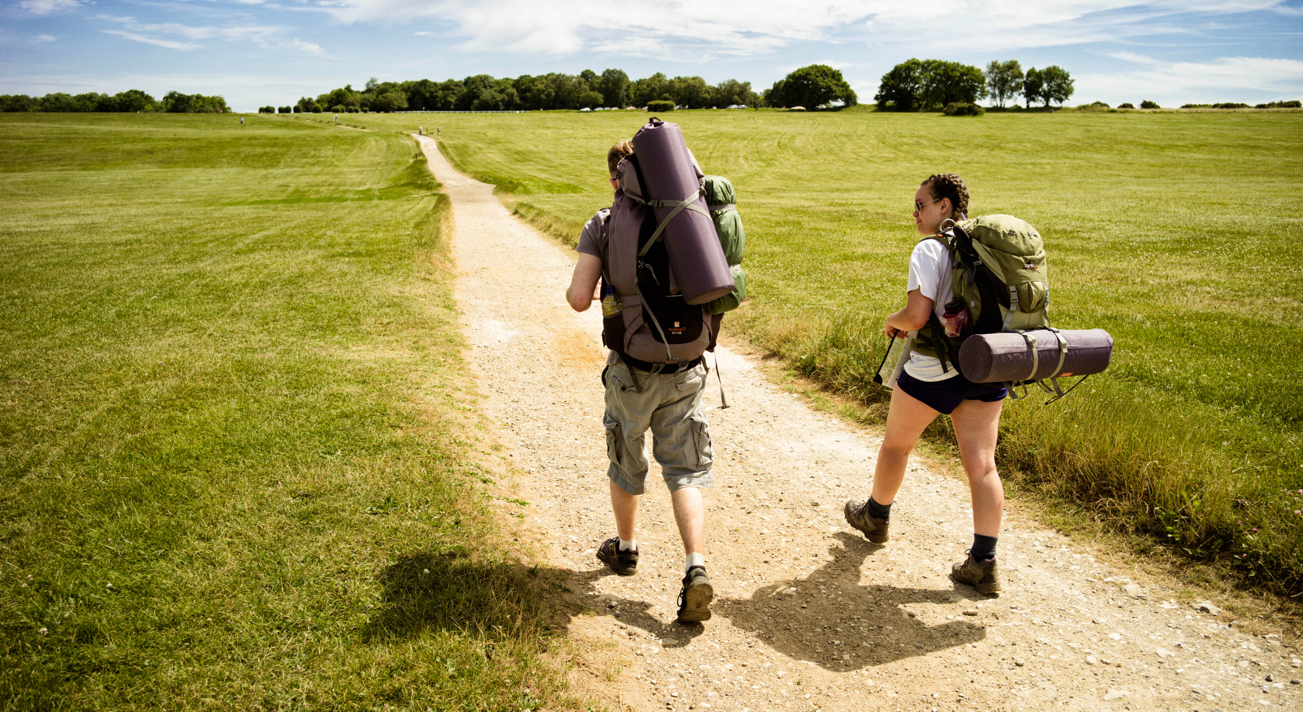 Two participants on expedition walking path with rucksacks on
