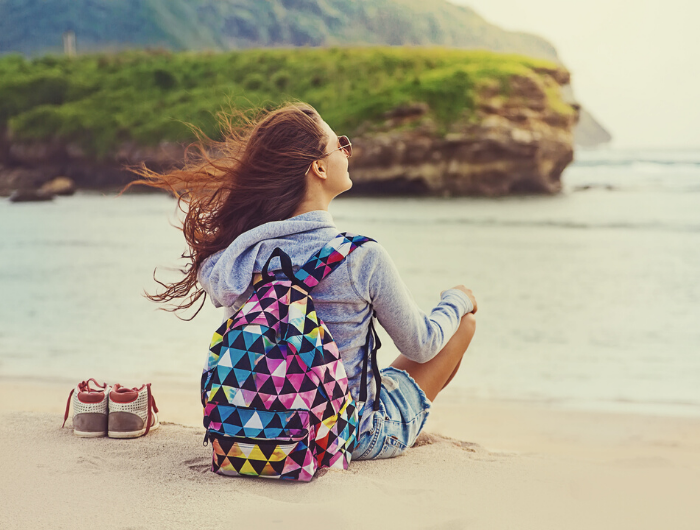 Young woman sitting on beach with backpack