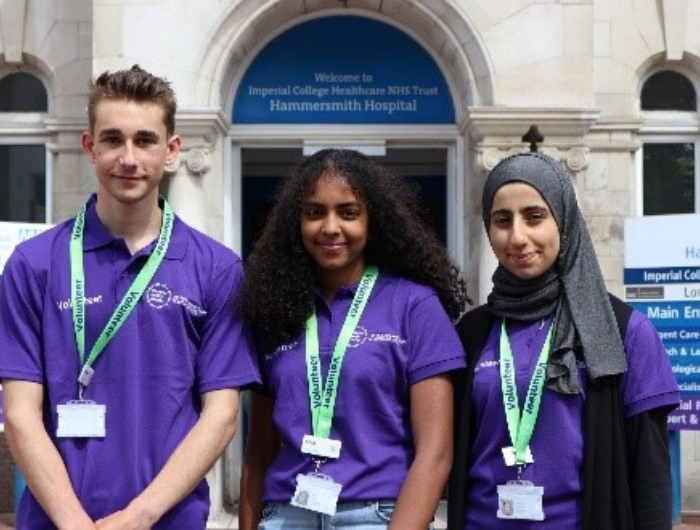 Three young DofE volunteers infront of NHS hospital wearing purple tshirts