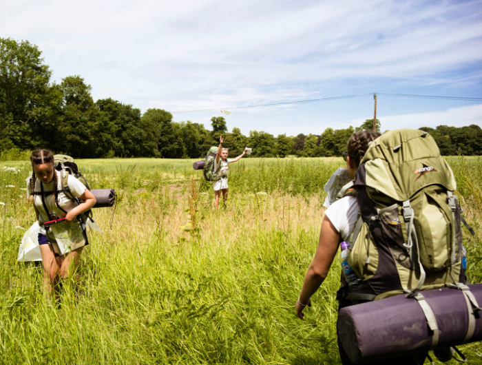 Three young women in green field on expedition wearing rucksacks